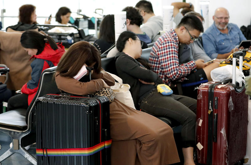 Passengers rest as their flights were cancelled because of Typhoon Hagibis at Haneda airport in Tokyo on Saturday.  (AP photo)