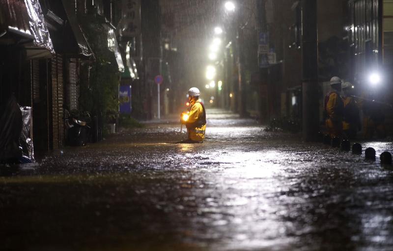 A firefighter makes his way through a flooded street in the residential area in Tokyo hit by Typhoon Hagibis on Saturday.(Kyodo News via AP photo)