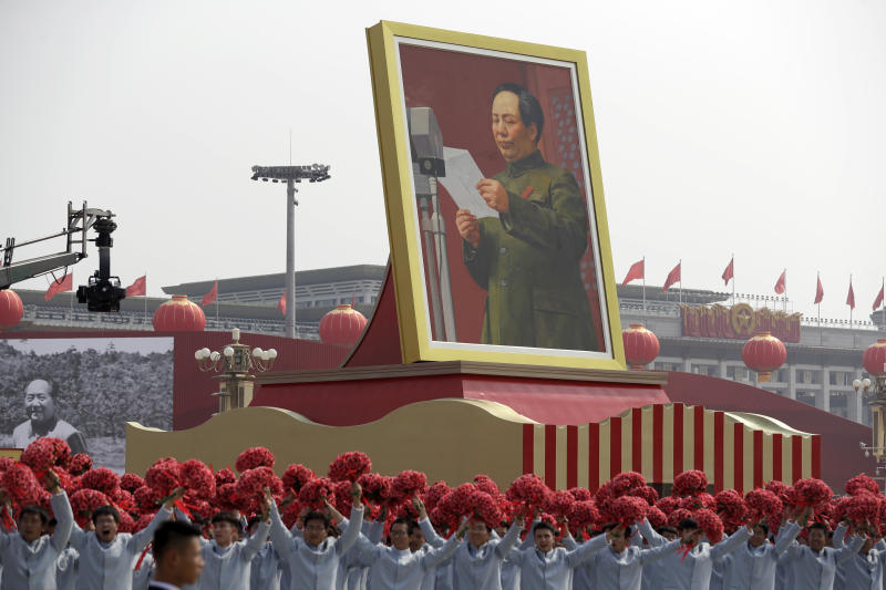 Participants wave floral bouquets as they march next to a large portrait of Chinese leader Mao Zedong during a parade commemorating the 70th anniversary of the founding of Communist China in Beijing, Oct 1, 2019. (Reuters file photo)