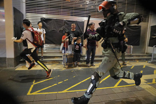 Police chase a person in Hong Kong on Sunday, as protesters changed tactics and popped up in small groups in multiple locations across the city. (AP photo)
