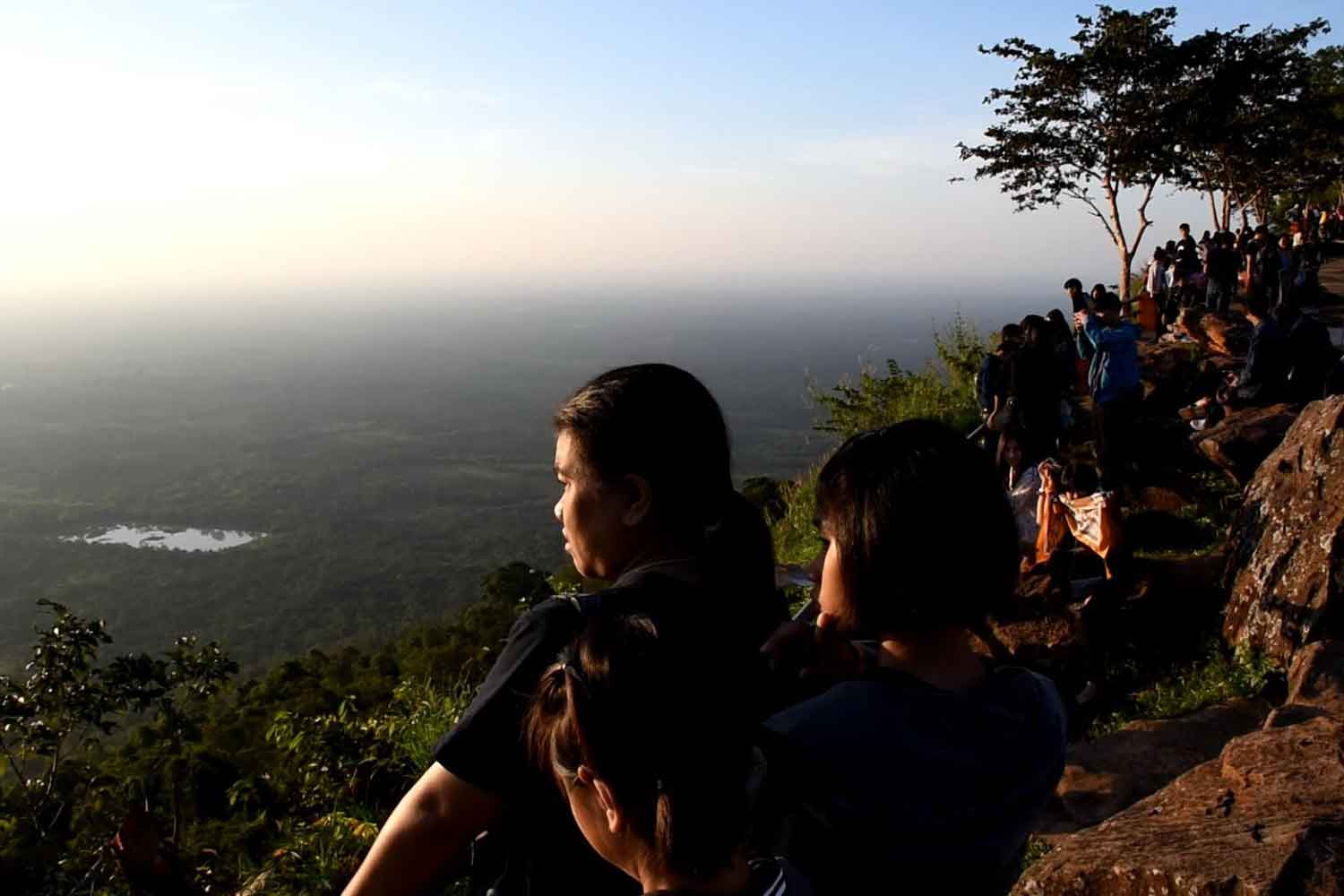 Tourists experience sunrise on Pha Mor E-Daeng cliff in Si Sa Ket province on Sunday. The Meteorological Department has announced the beginning of winter this Thursday. (Photo by Sanoh Worarak)