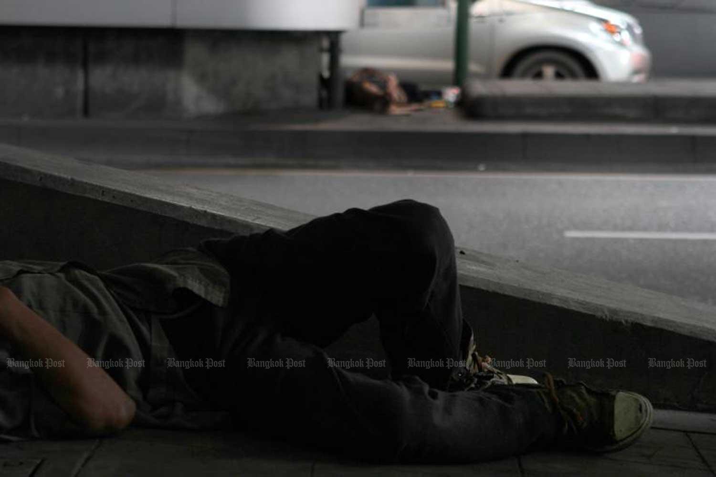 Homeless people sleep under a BTS electric train station in Thong Lor area on Sukhumvit Road, Bangkok. (Bangkok Post file photo)