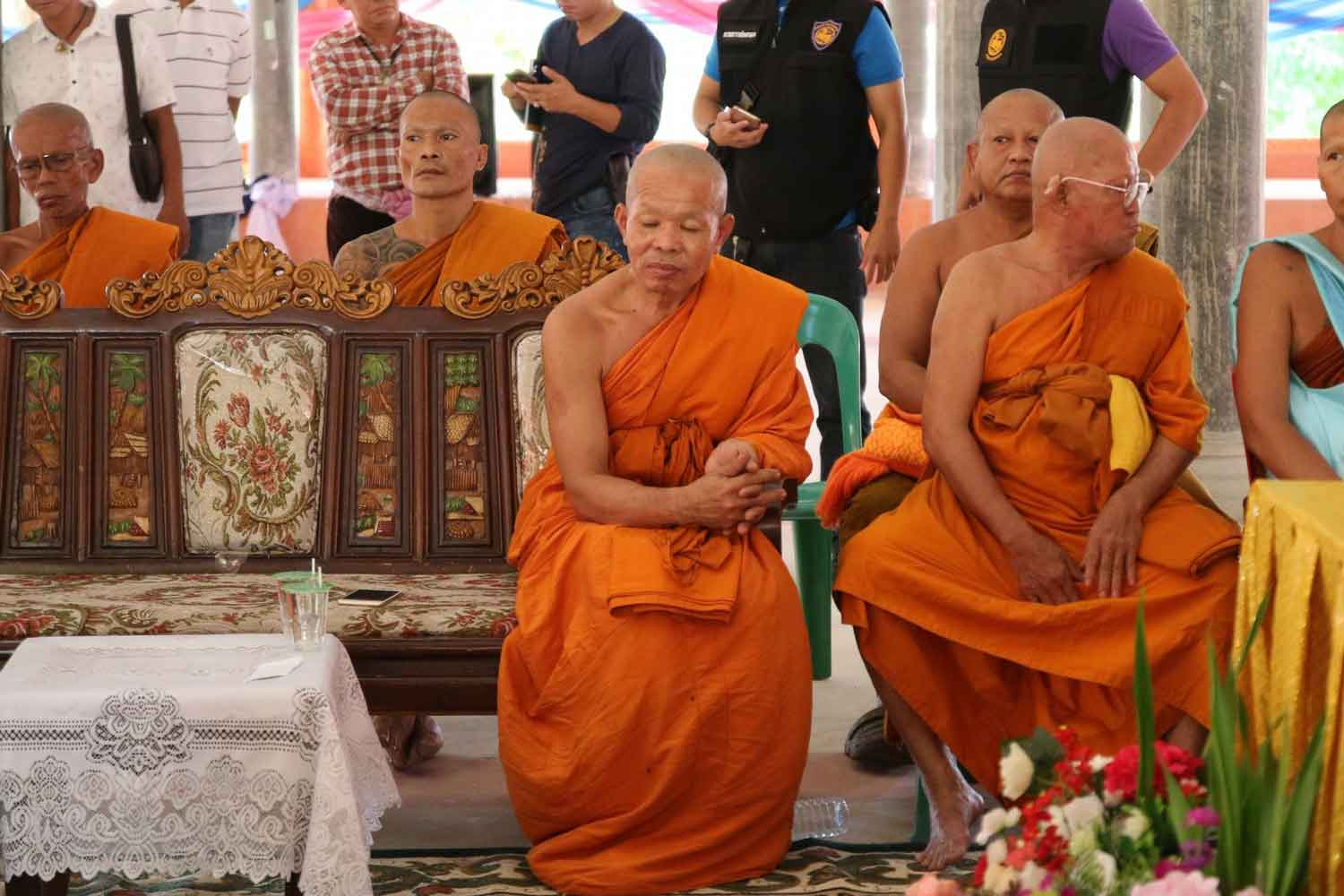 Phra Khru Sangkharakwinai Inthawinyo (seated right), 51, abbot of Wat Intharam in Tha Muang district of Kanchanaburi at a meeting on Tuesday with local monks, residents and officials, where he was accused of sexually abusing a 13-year-old novice. Phra Natthee Sirijantho, who reportedly rescued the young victim, sits beside him on the left. (Photo by Piyarat Chongcharoen)