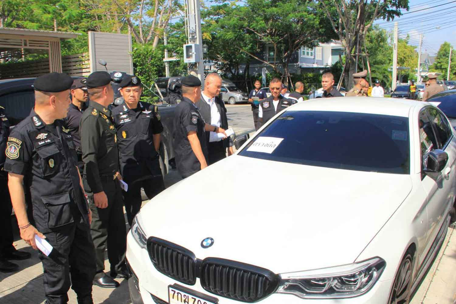 Narcotics suppression police seize a BMW car, along with other assets, at the house of a suspect in a major drug-money laundering operation, in Muang district of Samut Prakan on Wednesday. (Photo by Sutthiwit Chayutworakan)