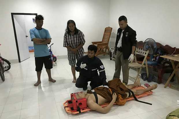 A medic helps severely wounded Phra Winai Sutthiyano after he was shot while burgling  a grocery shop in Ubon Ratana district of Khon Kaen province early Wednesday morning. The monk later died. (Photo by Chakkrapan Natanri)
