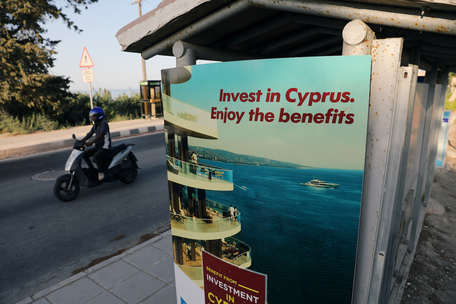 A motorcyclist passes an 'Invest in Cyprus' advertisement near Paphos, Cyprus. The Mediterranean country is a favourite destination of Hun Sen's wealthy relatives. (Reuters Photo)