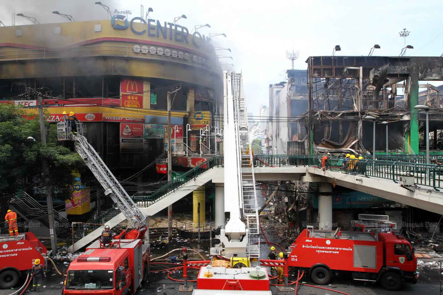 Firefighters extinguish the fire set by arsonists at the CentreOne shopping mall and Dok Ya bookstore at the Victory Monument in 2010. (File photo by Apichart Jinakul)