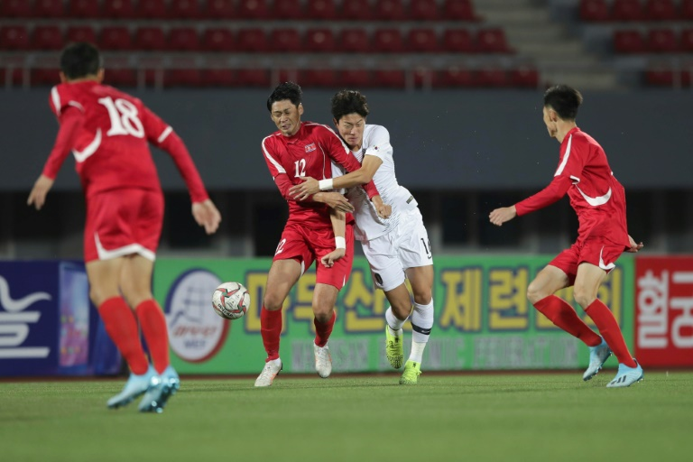 South Korea's Hwang Ui-jo and North Korea's Ri Yong Jik fight for the ball during the World Cup 2022 Qualifying match in Pyongyang.