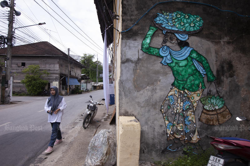 A woman walks past graffiti in the Pattani municipality. Representatives of the business community are pushing a train link with Malaysia to boost tourism in the southern border provinces. (Photo by Jestjaras Na Ranong)