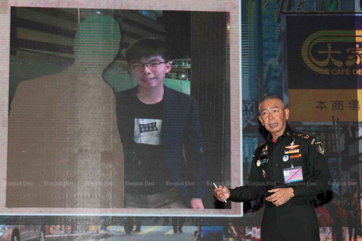 Army chief Gen Apirat Kongsompong shows a picture of Hong Kong activist Joshua Wong with the removed image of Future Forward leader Thanathorn Jungroongruangkit at a