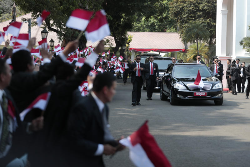 Palace staff wave Indonesian flags as the motorcade carrying President Joko Widodo leaves Merdeka Palace for the parliament building for his inauguration ceremony in Jakarta, Indonesia, on Sunday. (AP photo)