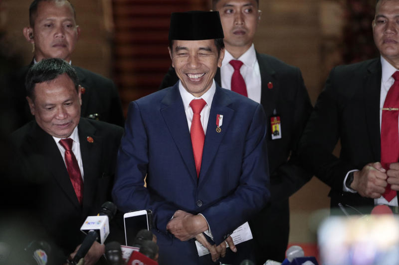 Indonesian President Joko Widodo, center, smiles as he speaks to the media upon arrival after his inauguration for his second term, at Merdeka Palace in Jakarta, Indonesia, on Sunday. (AP photo)