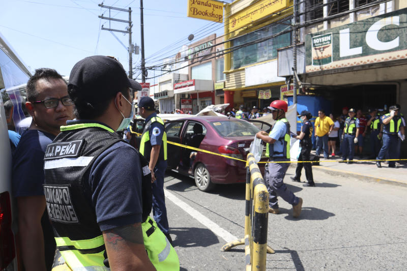 In this Oct 18, 2019 handout photo provided by the Olongapo Public Information Office, police check on an Australian named Anthony George inside a car in Olongapo, northern Philippines. Philippine police city director of Olongapo city said they arrested Australian Michael McLaren shortly after the incident for the alleged killing of George and Filipino Mila Bailey inside the car. Another Australian victim, Wayne Bailey, is still recovering at the hospital from gunshot wounds. (Olongapo Public Information Office via AP)