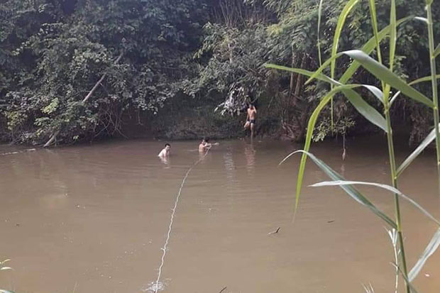 Rescuers and park rangers search for Wissanu Kluanmuangpak after he was swept away while   swimming across Klong Lamphayatharn in Na Di district of Prachin Buri province on Tuesday. (Photo by Manit Sanubboon)