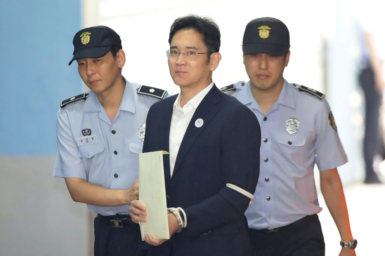 Samsung Group heir Lee Jae-yong arrives at Seoul Central District Court in handcuffs during his trial in 2017.