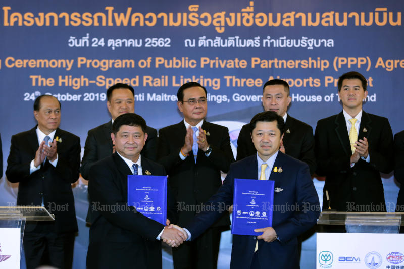Acting head of the State Railway of Thailand Worawut Mala (left) and Charoen Pokphand Group chief executive officer Suphachai Chearavanont with the signed contracts for the  construction of a high-speed train linking three airports, at Government House. (Photo by Chanat Katanyu)