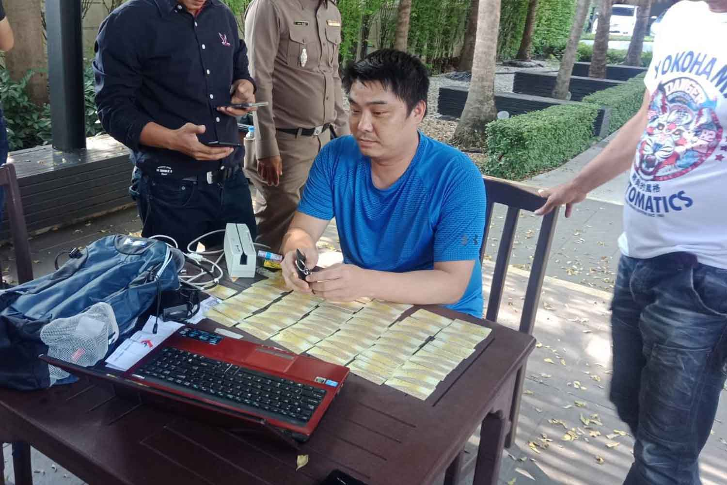 Police hold Feng Yi Sheng, 36, outside his condominium in Huai Khwang, with the forged cards and other equipment seized from his room. (Photo supplied)