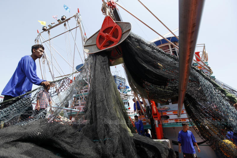 Fishermen use a machine to haul in a fishing net onto a boat in Pattani in August. (Bangkok Post photo)