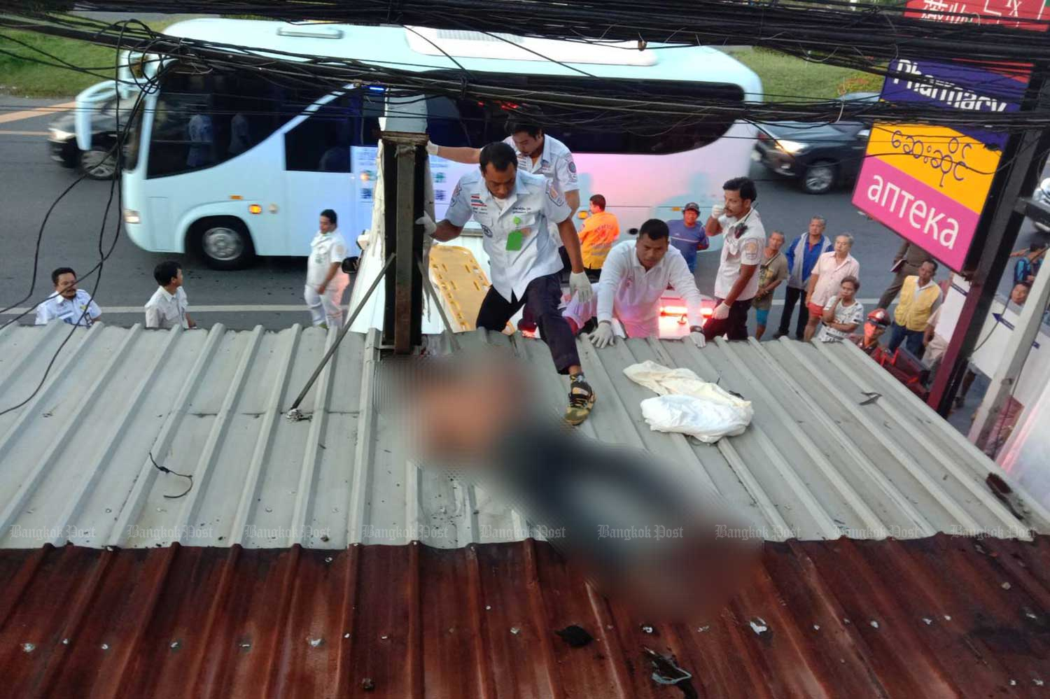 Rescue workers prepare to remove the body of a man from the awning of a shop in Thalang district, Phuket. (Photo by Achadtaya Chuenniran)