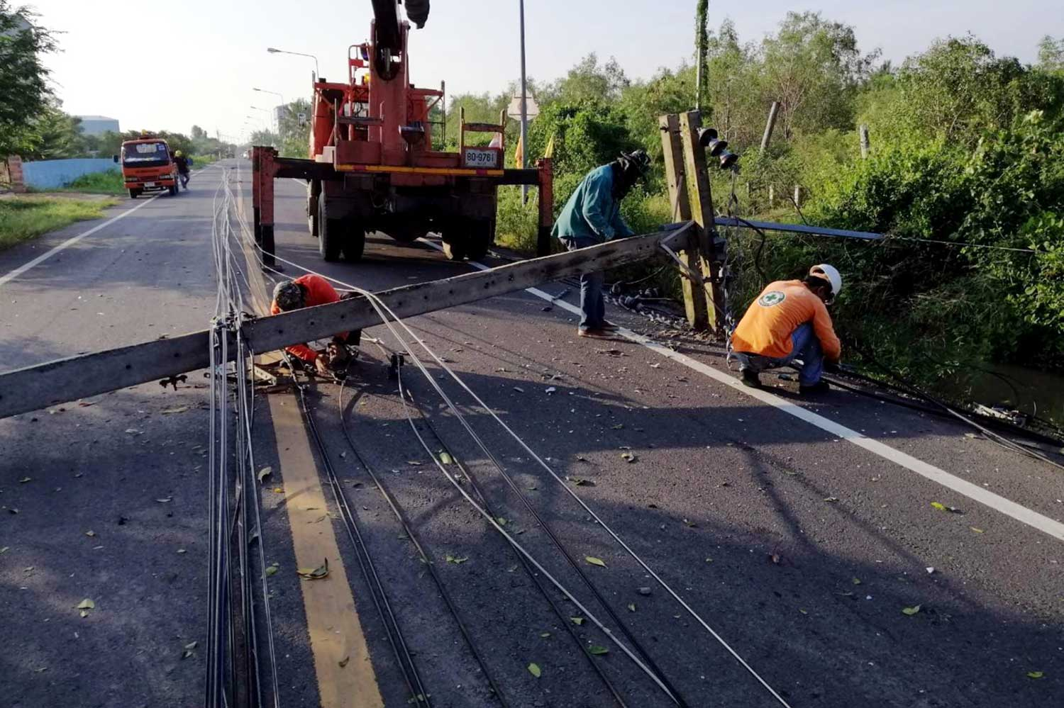 Workmen labour to clear the road and restore power on Wednesday after the storm hit Ban Laem district in Phetchaburi province on Tuesday night. (Photo by Chaiwat Satyaem)