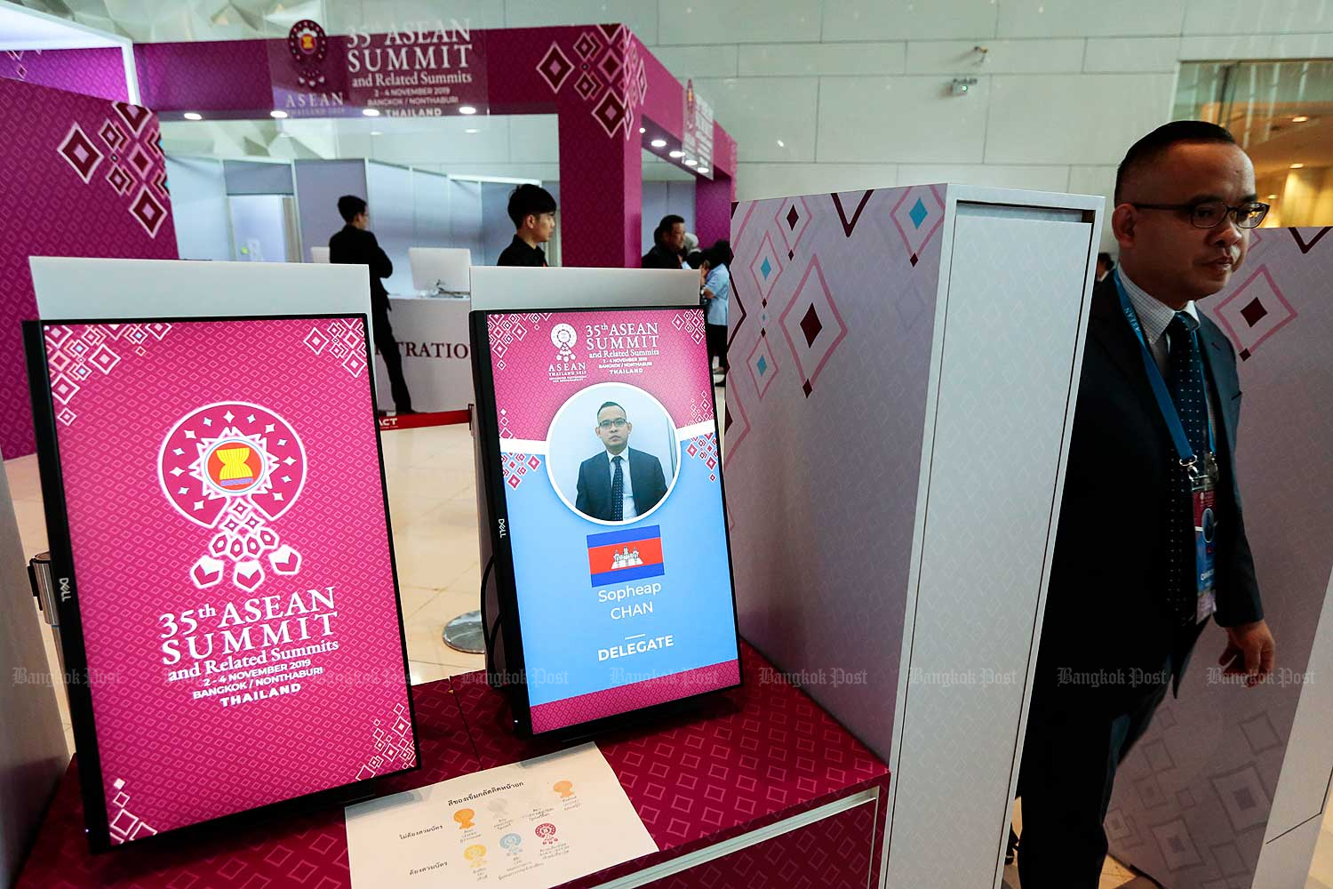 Screened on screen: The name and photo of a Cambodian participant at the 35th Asean Summit appear on the screen as he walks through a Radio Frequency Identification reader installed to tighten security at the Impact Exhibition and Convention Centre in Nonthaburi yesterday. (Photo by Patipat Janthong)