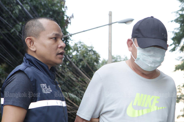 A policeman from the Anti-Trafficking in Persons Division escorts Supat Santipiyakul for detention at the Criminal Court on Monday. (Photo by Apichit Jinakul)