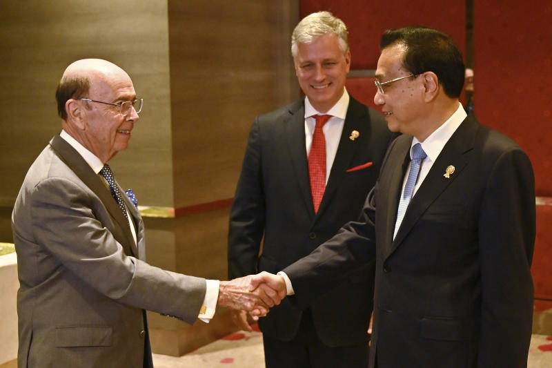 US Commerce Secretary Wilbur Ross, left, shakes hands with China's Premier Li Keqiang, right, as US National Security advisor Robert O'Brien watches during a bilateral meeting in Bangkok on Monday, on the sidelines of the 35th Association of Southeast Asian Nations (Asean) summit. (AP photo)
