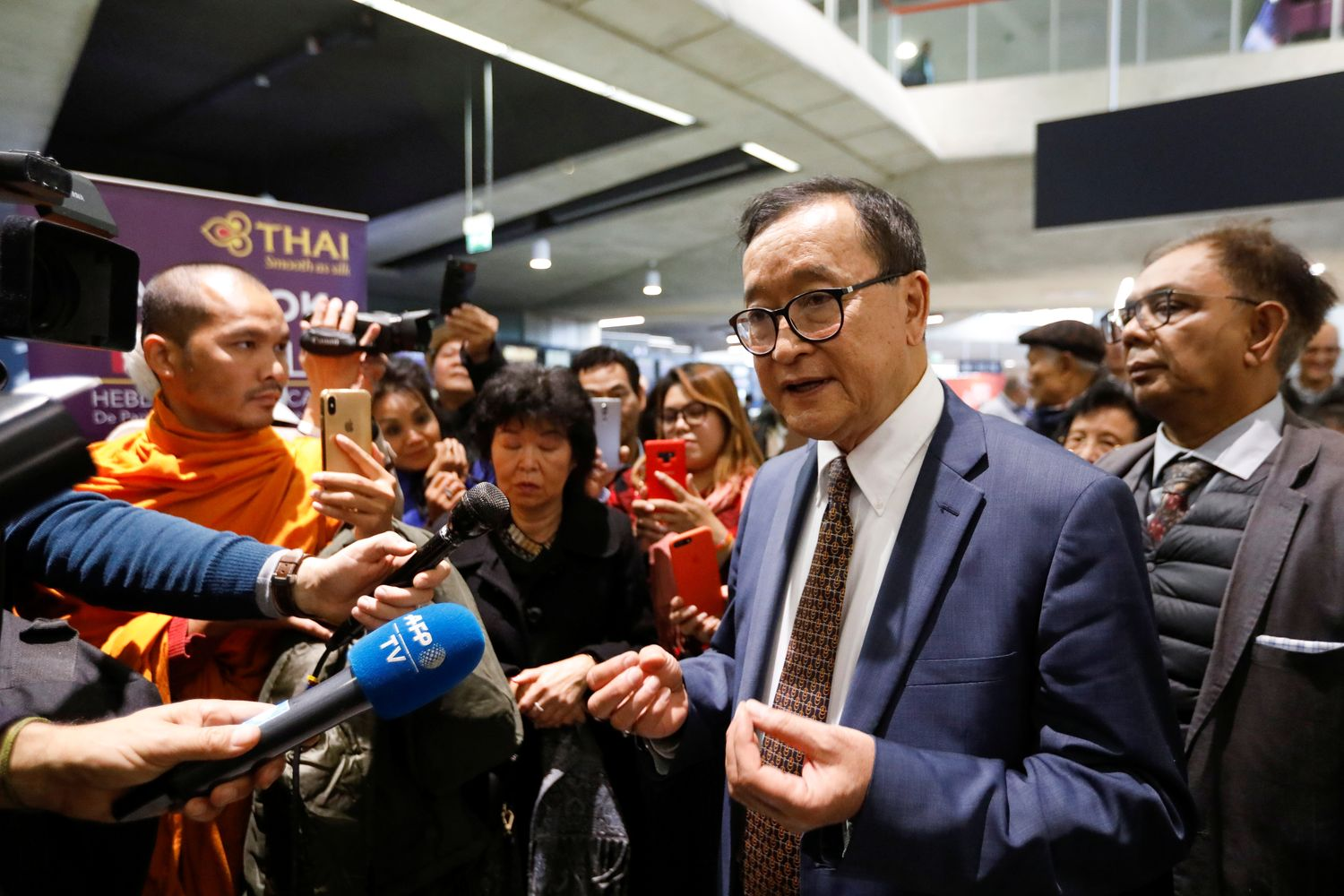 Cambodia's self-exiled opposition party founder Sam Rainsy, who has vowed to return to his home country, talks to supporters after being prevented from checking-in for a flight from Paris to Bangkok at Roissy Airport in Paris on Thursday. (Reuters photo)