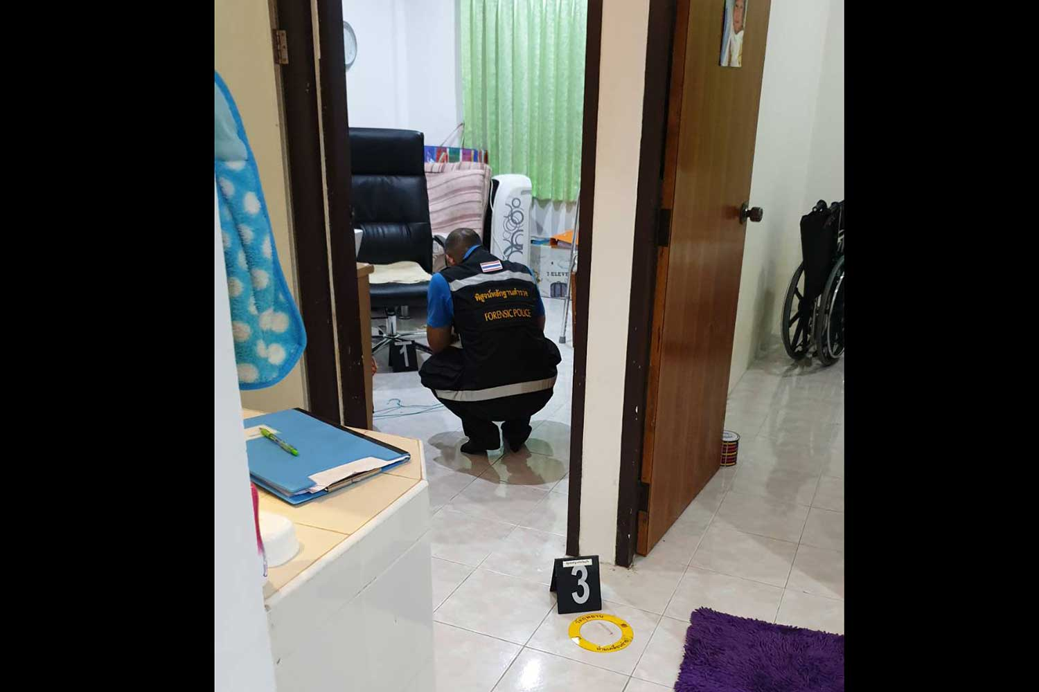 A forensic officer examines the scene of the robbery at the house where a German man was tied up and cut by two men who robbed him and his Thai wife in Muang Phuket on Thursday evening. (Photo supplied)