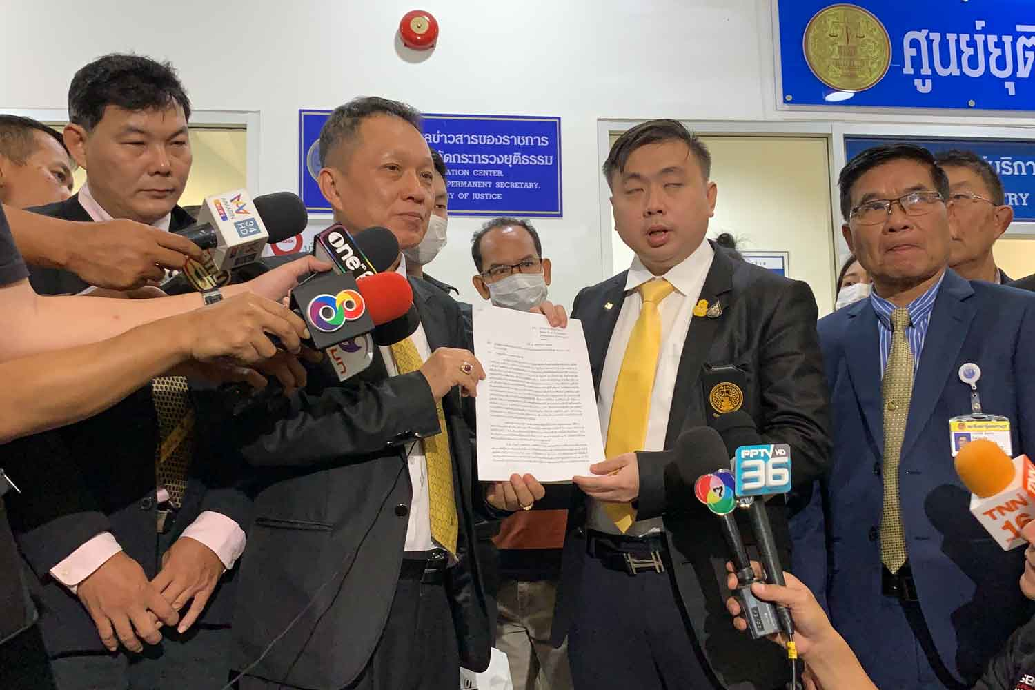 Lawyer Worakorn Pongthanakul, centre left, hands a request for assistance from vendors who faced