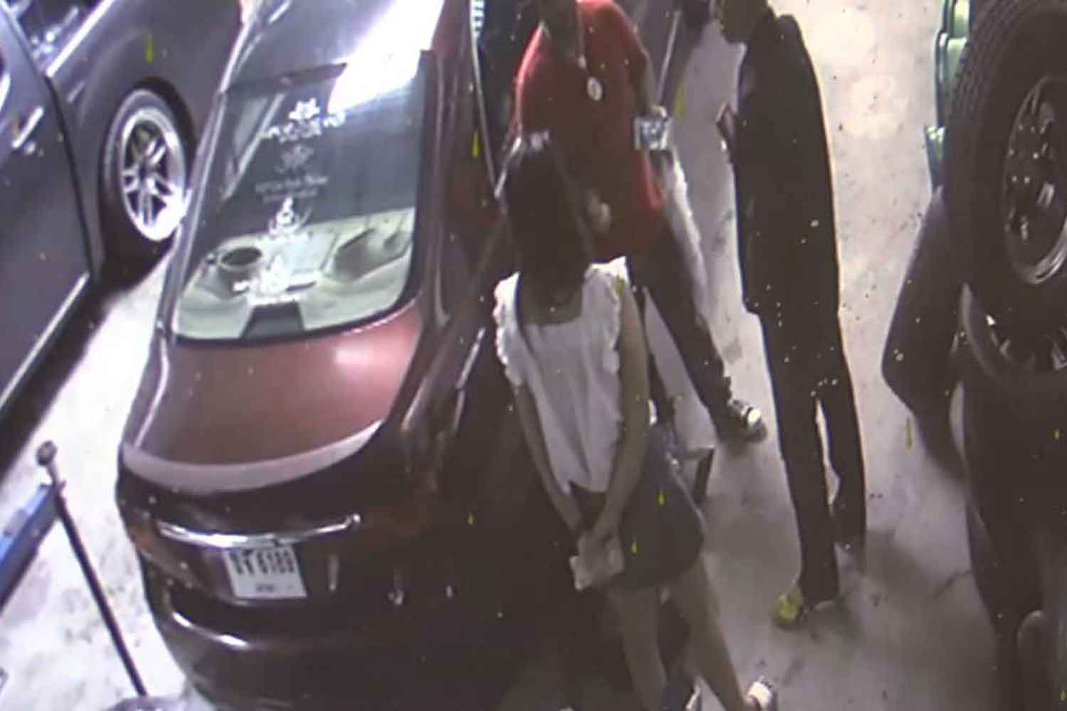 Security camera footage shows the owner of an auto tyre shop in Nakhon Si Thammarat holding cash while talking with men she said claimed to be police officers who demanded money in exchange for sparing the shop from being prosecuted. (Photo supplied)