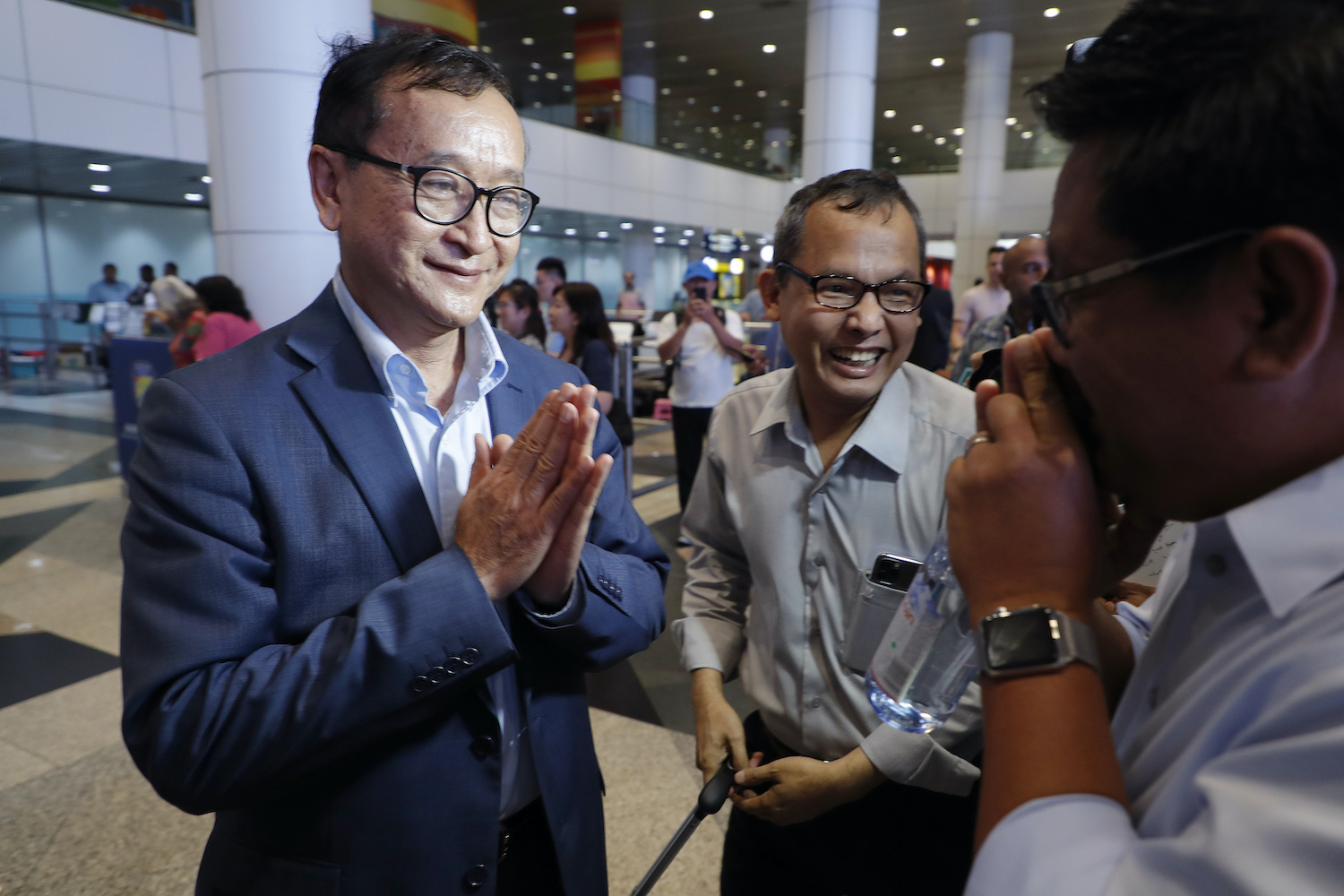 Sam Rainsy greets supporters after arriving at Kuala Lumpur International Airport in Malaysia on Saturday. (AP photo)