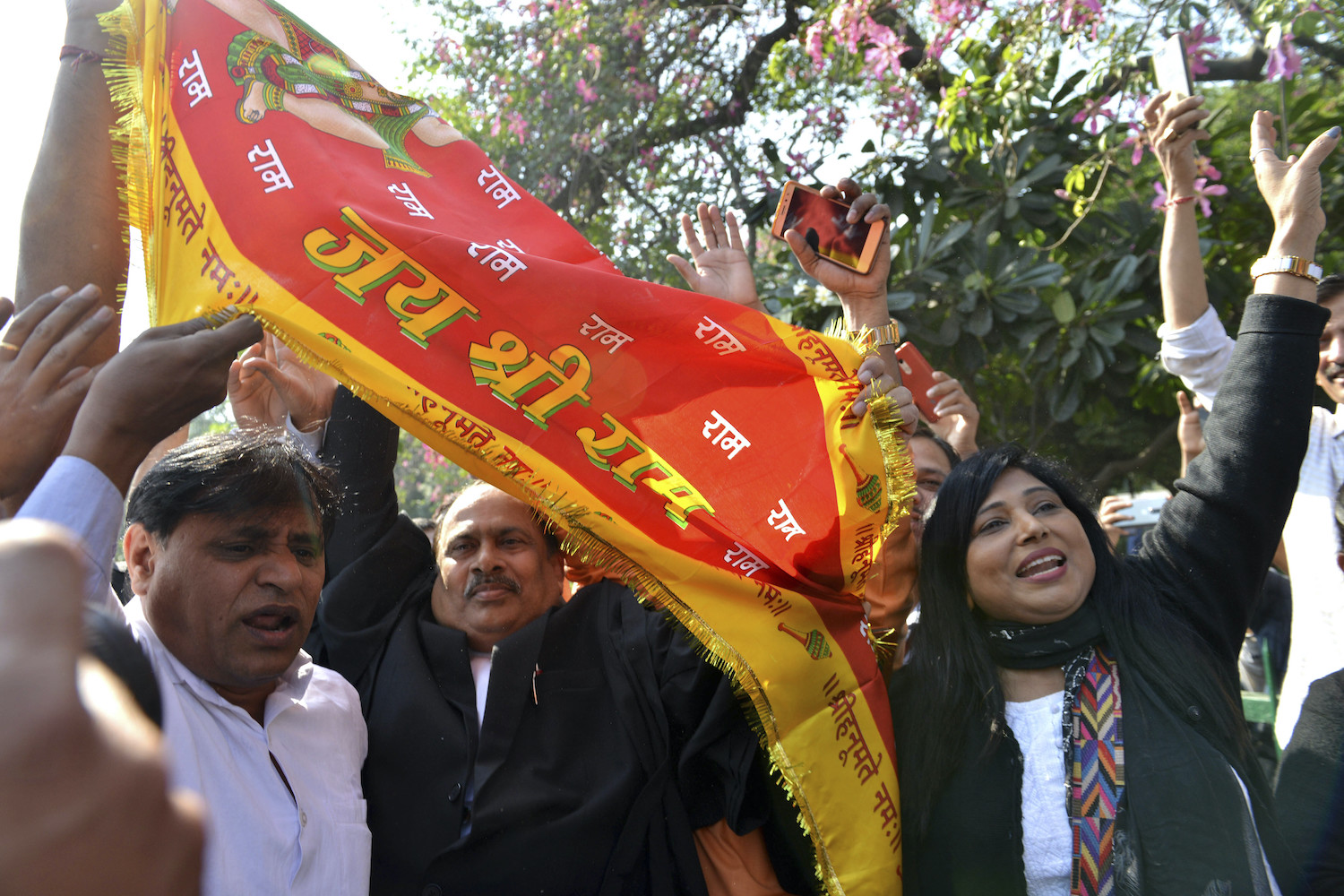 """People wave a flag that reads """"Glory to Lord Ram"""" as they celebrate the Ayodhya ruling outride the Supreme Court in New Delhi on Saturday. (AP Photo)"""