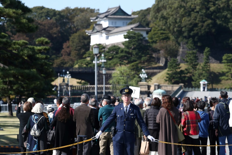 Police officers stand guard around Japan's Imperial Palace ahead of Sunday's parade.