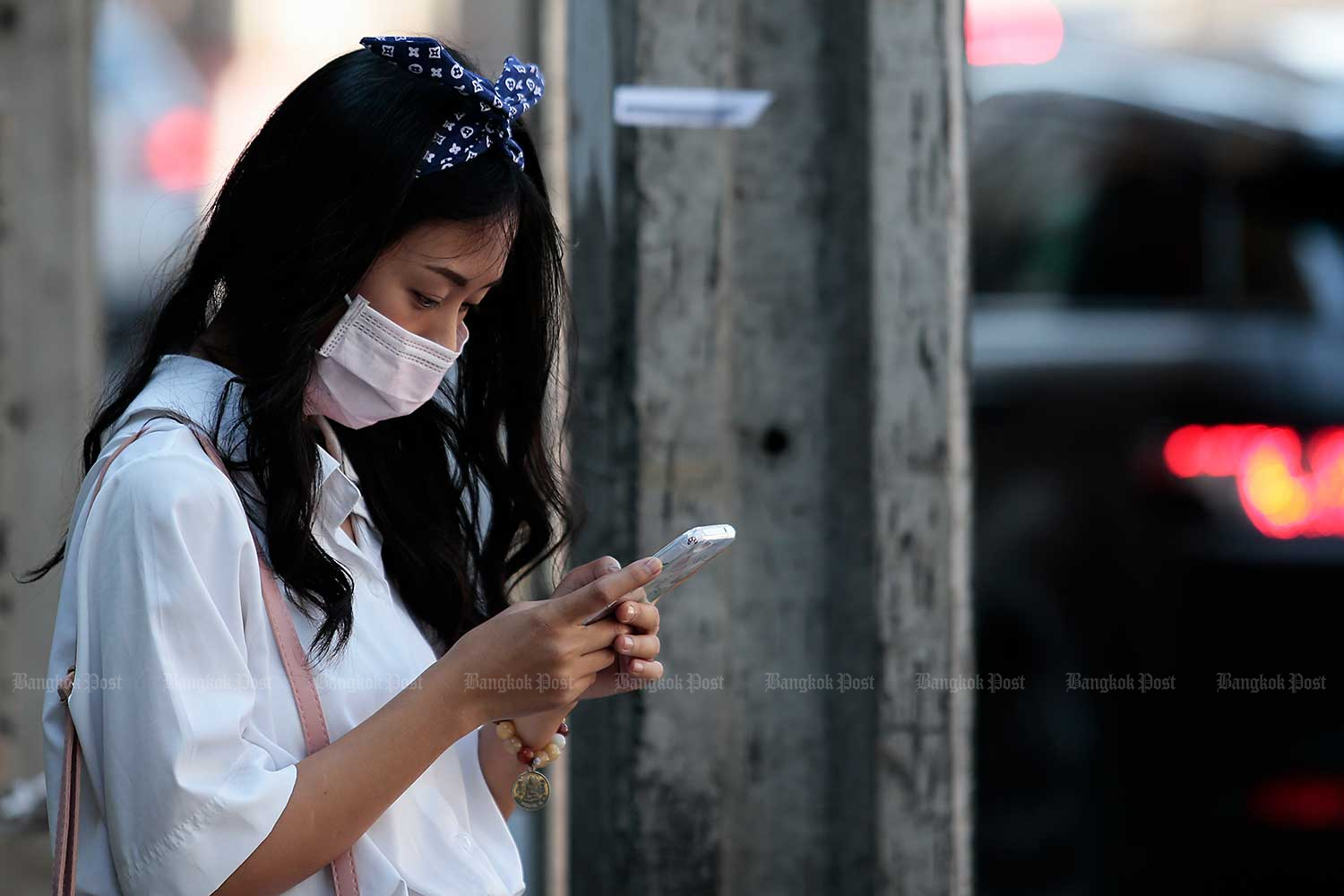 A student checks her smartphone. (Photo by Patipat Janthong)