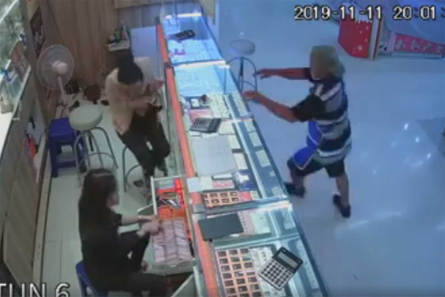 A lone man throws stones to smash display cabinets and steal gold from a shop at a Tesco Lotus superstore in Udon Thani on Monday night. (From video on ๑udonthaniupdate Facebook page)