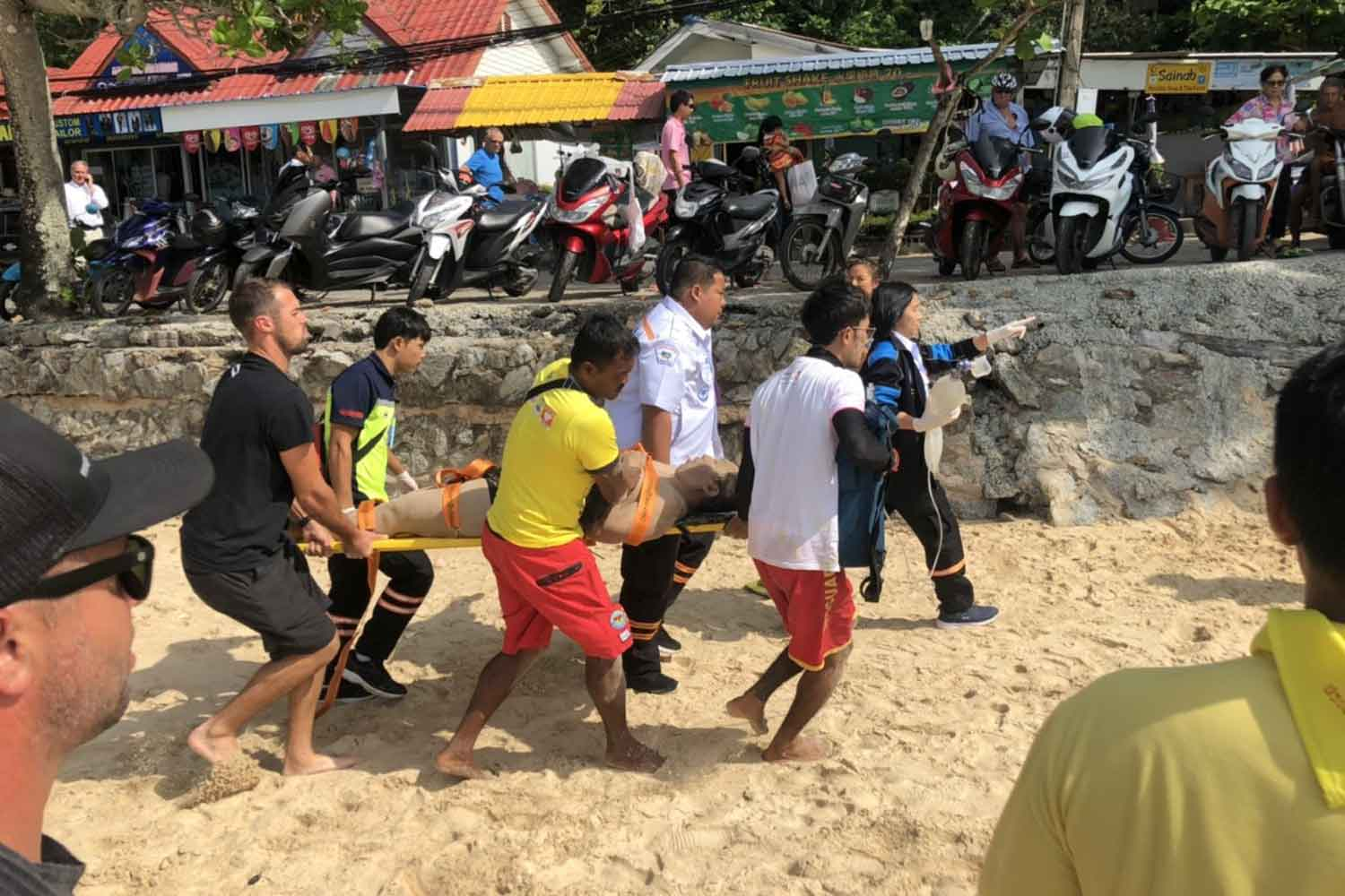 Chinese tourist Dong Xuyan is rushed to a hospital after being rescued from the sea off Nai Harn Beach in Phuket on Tuesday morning. (Photo by Achadtaya Chuenniran)