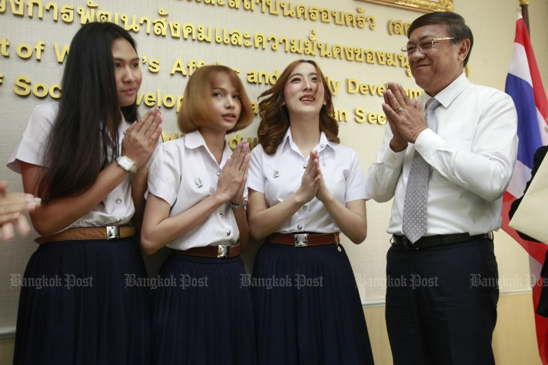 From left, Chulalongkorn University students Pichet Puenintr, Nattha Boonmanit, Jirapat Techakijvekin submit their petition for permission to wear student uniform in accordance with their gender identity to department of women's affairs and family development chief Lertpanya Buranabundit.