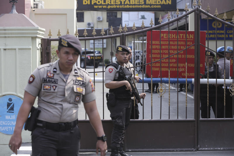 Police officers stand guard at the gate of the local police headquarters following a suicide bombing attack at the compound in Medan, North Sumatra, Indonesia, on Wednesday. (AP photo)