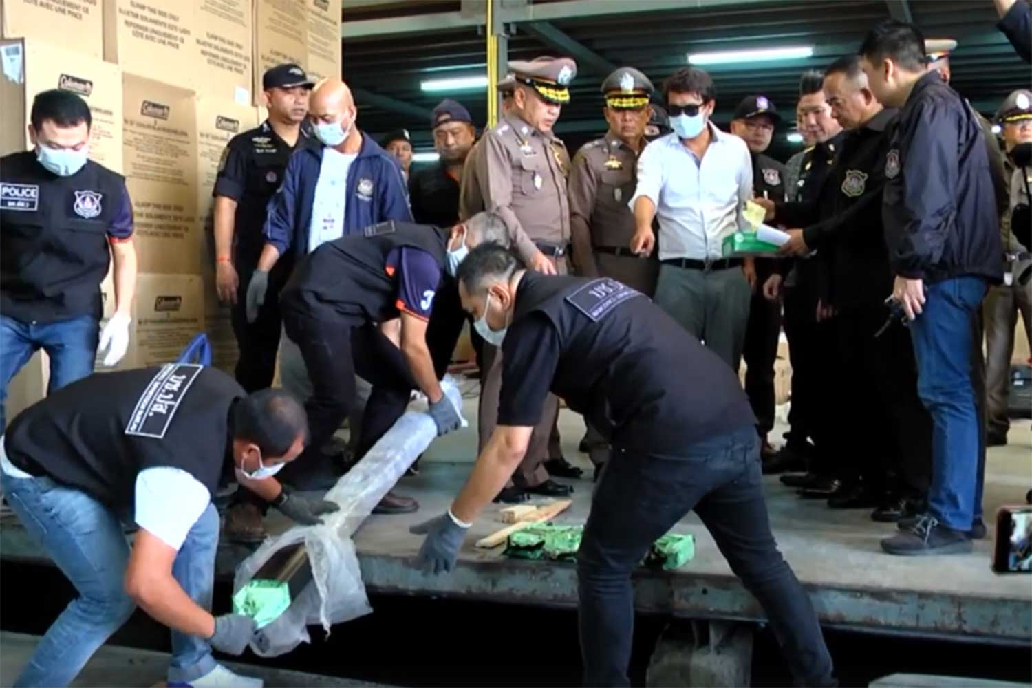 Narcotics Suppression Bureau officials find packets of crystal methamphetamine hidden inside the frame of a treadmill. More than 200kg of crystal methamphetamine were found inside the frames of 10 treadmills labelled for shipment to Japan, during a raid on a godown in Bangkok's Prawet district on Thursday. One man was arrested. (Capture from TV Channel 8)