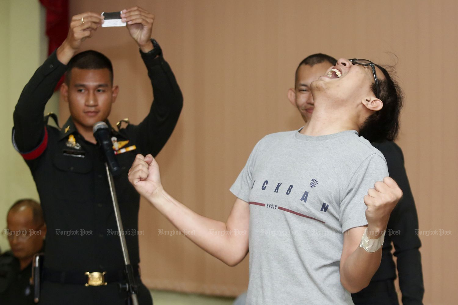 A man reacts after drawing a black card, which means he will not be drafted, at a recruiting station in Pomprap Sattruphai district, Bangkok, on April 1, 2018. (Photo by Pattarapong Chatpattarasill)