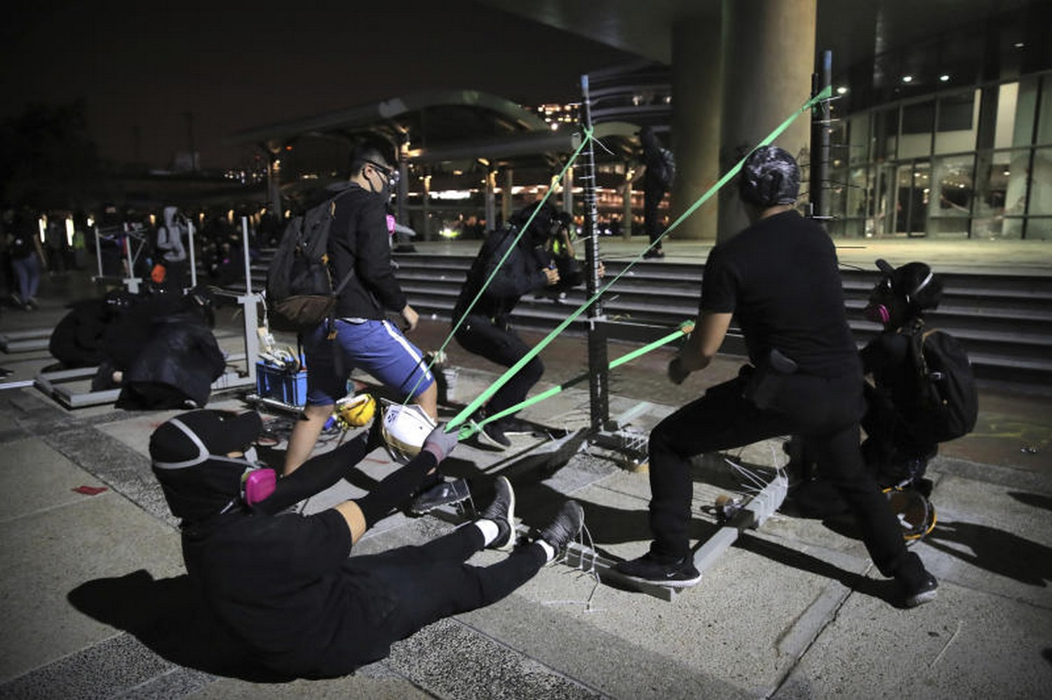 Protesters practice using a homemade slingshot at Hong Kong Polytechnic University in Hong Kong on Thursday. Police warned protesters they were moving