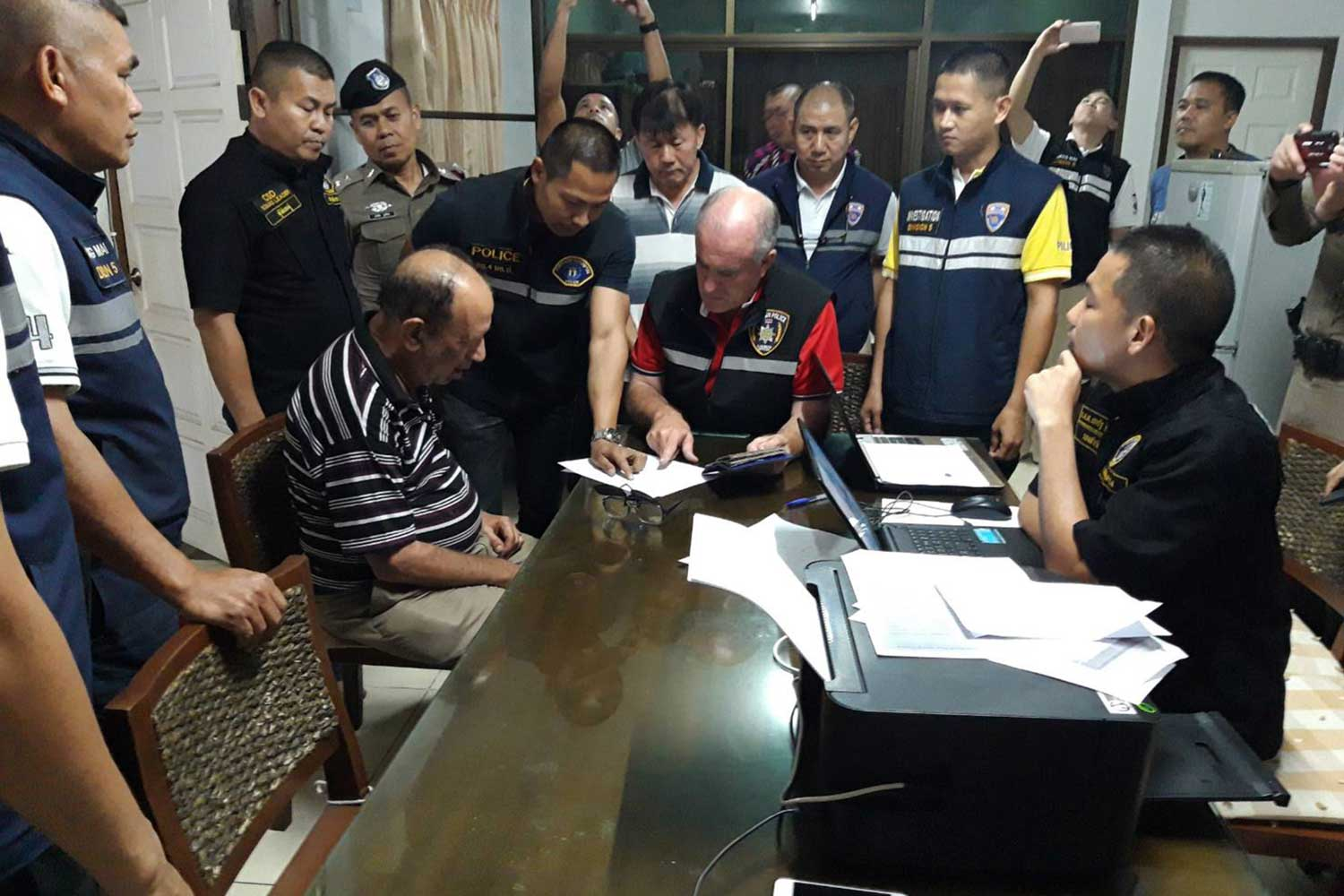 American national Bruce Michael Fein, 75, seated left, is questioned by Crime Suppression Division police with the assistance of an interpreter, centre. (Crime Suppression Division photo)
