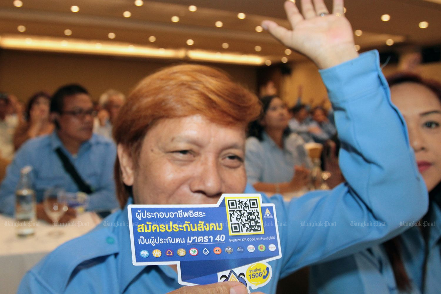 A man shows off a sign saying the SSO safety net is now extended to cover independent workers such as taxi and motorcycle taxi drivers last year. (Bangkok Post file photo)