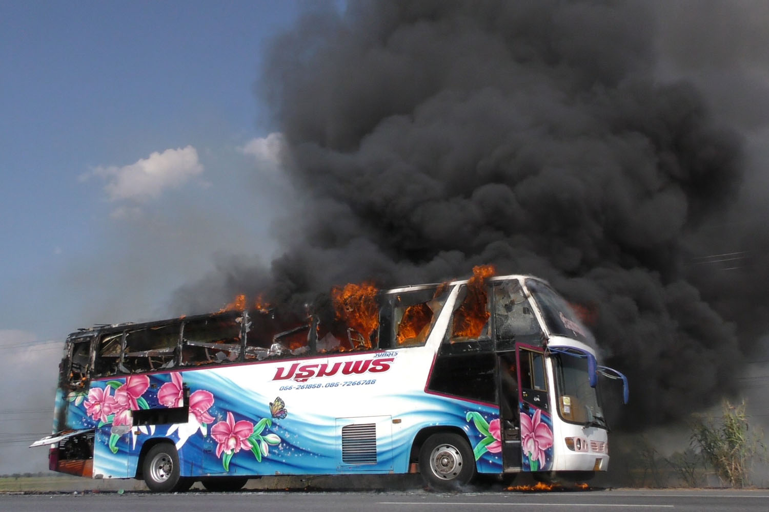 An air-conditioned bus catches fire on Asia Highway in Manorom district of Chai Nat province on Sunday. (Photo by Chudate Seehawong)