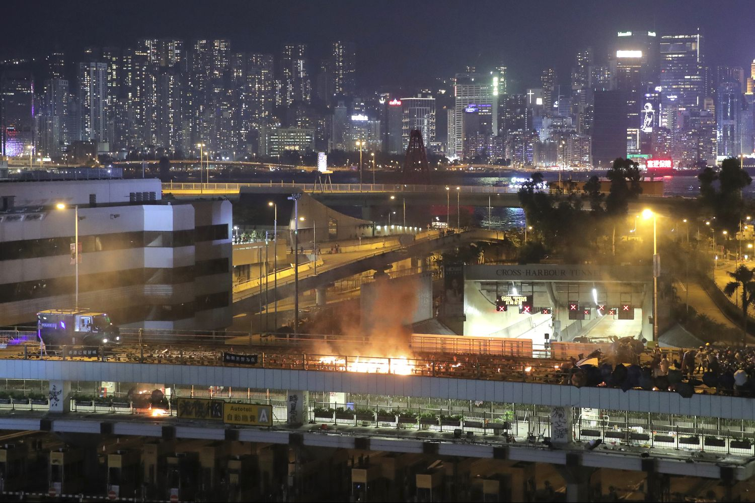 An armored police vehicle (left) approaches a burning barricade built by protestors near the entrance to the Cross Harbour Tunnel in Hong Kong on Sunday. (AP photo)
