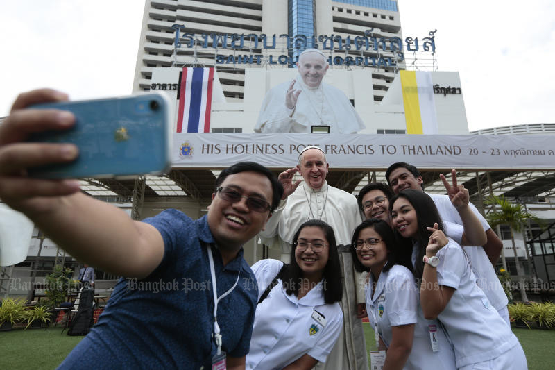 People take photos with a cutout of Pope Francis at Saint Louis Hospital on Thursday. (Photo by Patipat Janthong)