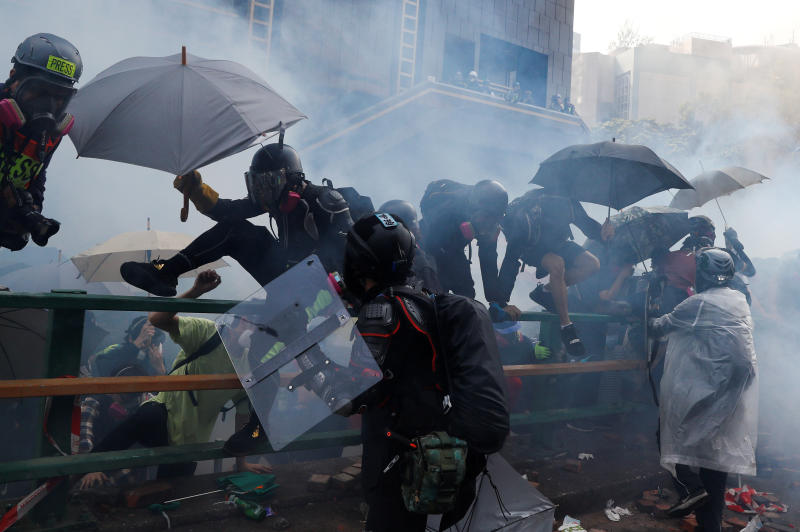 Protesters attempt to escape from tear gas while trying to leave the campus of Hong Kong Polytechnic University during clashes with police in Hong Kong on Monday. (Reuters photo)