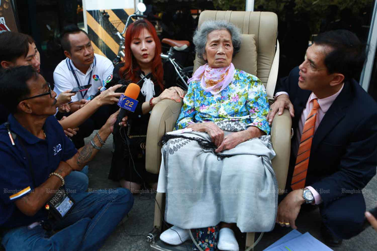 Huay Sriwirat, 76,  at the Phra Khanong Civil Court in Bangkok on Tuesday with her granddaughter Mintra Sriwirat, left, and lawyer Anantachai Chaiyadet, right. (Photo by Somchai Poomlard)