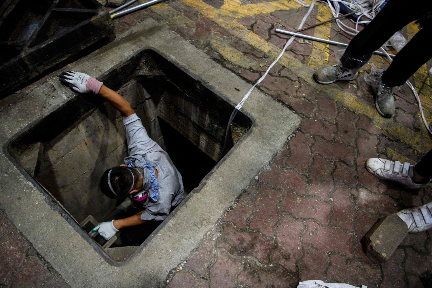 A protester climbs down into a sewer entrance with a guide string as he and others try to find an escape route from the Hong Kong Polytechnic University in the Hung Hom district of Hong Kong, early Tuesday. (Photo by AFP)